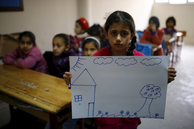 Syrian refugee girl Nur El-Huda, 9, shows a drawing of her home in Syria, in her classroom in Yayladagi refugee camp in Hatay province near the Turkish-Syrian border, Turkey, December 16, 2015. (Photo by Umit Bektas/Reuters)