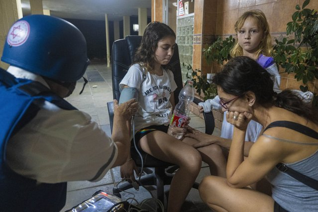 An Israeli paramedic checks the blood pressure of a young girl at residential building after it was hit by a rocket fired from Gaza Strip, in Ashkelon, southern Israel, Wednesday, May 12, 2021. (Photo by Tsafrir Abayov/AP Photo)