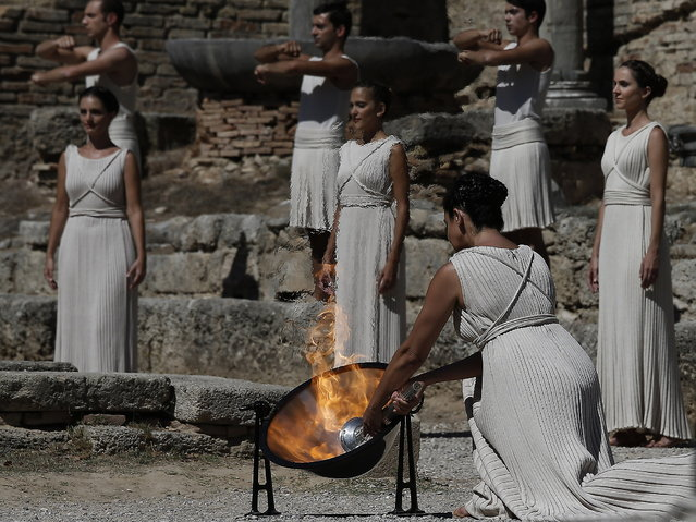 Actress Ino Menegaki as high priestess, lights the Olympic Flame from the sun's rays, during the lighting of the Olympic flame at Ancient Olympia, in west southern Greece on Sunday  September 29, 2013. Using the sun's rays at the birthplace of the ancient Olympics, organizers carried out a successful ceremony to light the flame for the 2014 Sochi Winter Olympics February 7–23, 2014 in Russia. (Photo by Dimitri Messinis/AP Photo)