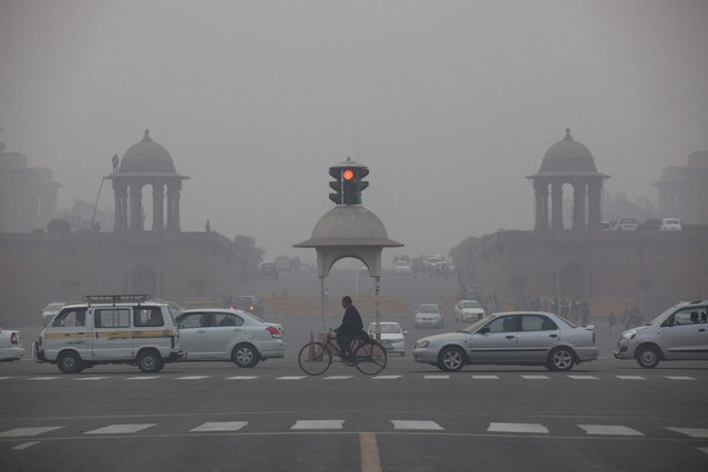 Vehicles move past the Presidential Palace as smog engulfs the evening in New Delhi, India, Wednesday, January 13, 2016. The World Health Organization last year named New Delhi the world's most polluted city. The pollution is at its worst in the winter, when winds die down and dense smog often engulfs the city in the morning. (Photo by Tsering Topgyal/AP Photo)