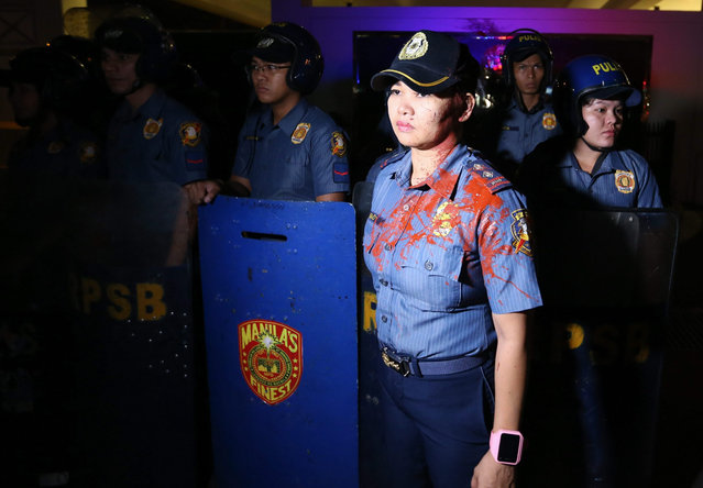 Filipino police senior inspector Rodeliza Naoy (3-R) stands guard after getting hit by a paint bomb during a lightning rally against the legality of the Enhanced Defense Cooperation Agreement (EDCA) in front of the US Embassy in Manila, Philippines, 20 January 2016. An agreement allowing the increased presence of US military forces for training in the Philippines is constitutional, the South-East Asian country's Supreme Court decided. The decision came amid increasing tension between China and the Philippines over a territorial row in the South China Sea. (Photo by Mark R. Cristino/EPA)