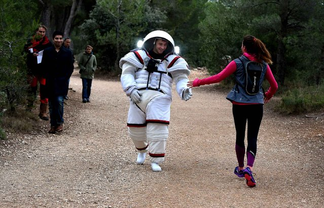 "Aeronautics and Space engineer at France's Compagnie Maritime d'Expertises, or Comex, Arnaud Prost (C) meets with a jogger as he tests on the ground the ""Gandolfi 2"" underwater training suit for spacewalk, on January 20, 2016 in the calanques region (rocky inlets) of Marseille. The underwater training suit ""Gandolfi 2"", developed with the European Space Agency (ESA), is designed for training astronauts underwater to simulate space gravity for the astronaut's extravehicular activities (EVAs). (Photo by Boris Horvat/AFP Photo)"