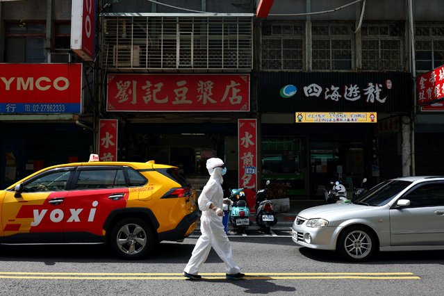 A person dressed in protective suit walks down a street following the recent surge of coronavirus disease (COVID-19) infections in Taipei, Taiwan, June 2, 2021. (Photo by Ann Wang/Reuters)