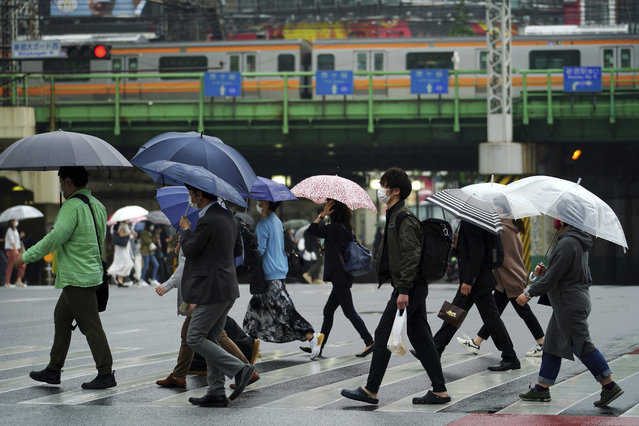 People wearing protective masks to help curb the spread of the coronavirus walk along a pedestrian crossing Thursday, May 13, 2021, in Tokyo. The Japanese capital confirmed more than 1,000 new coronavirus cases on Thursday. (Photo by Eugene Hoshiko/AP Photo)