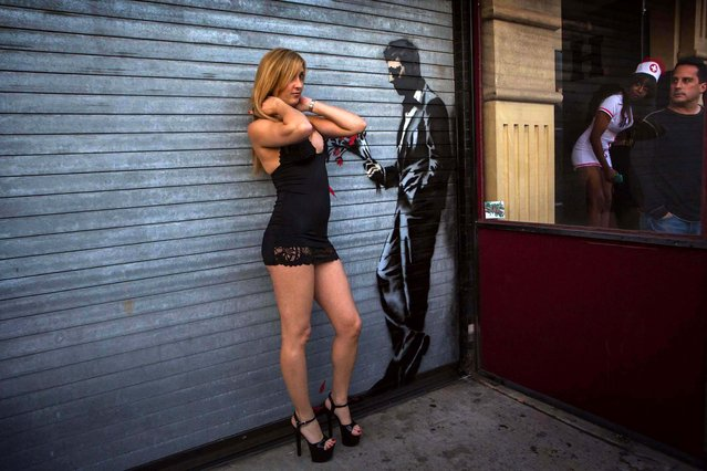 A dancer poses with the Banksy painting. (Photo by Eric Thayer/Reuters)