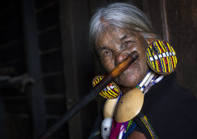 A tattooed woman plays a wooden  flute with her nose , in February, 2015, in Myanmar, Burma. With spider webs, B-patterns and crossed lines painstakingly inked on their faces these stunning photographs show the tattooed women of Burma. (Photo by Eric Lafforgue/Barcroft Media)