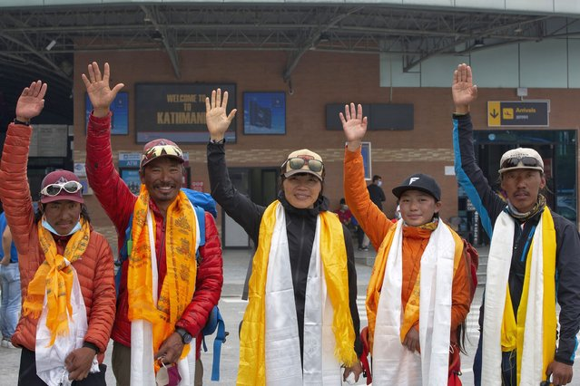 Tsang Yin-hung, 45, center, of Hong Kong who scaled Mount Everest from the base camp in 25 hours and 50 minutes, and became the fastest female climber and her team wave to the media as they arrive in Kathmandu, Nepal, Sunday, May 30, 2021. The Hong Kong teacher and retired attorney from Chicago who became the oldest American to scale Mount Everest, on Sunday returned safely from the mountain where climbing teams have been struggling with bad weather and a coronavirus outbreak. (Photo by Bikram Rai/AP Photo)