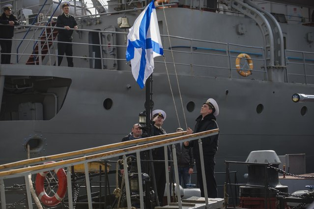 In this Thursday, March 20, 2014 file photo officers of the Ukrainian navy ship Lutsk raise a Russian navy flag aboard the Lutsk, which has been seized by Russia, in Sevastopol, Crimea. (Photo by Andrew Lubimov/AP Photo)