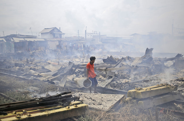 A man stands amid the rubble of houses burned down by a fire that razed through a slum in Jakarta, Indonesia, Tuesday, January 26, 2016. Fire is a frequent occurrence in Jakarta's slums which often have jury-rigged electrical connections and little or no safety features. (Photo by Dita Alangkara/AP Photo)