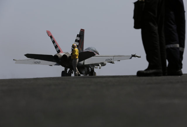 A U.S. military plane takes off from the flight deck of the USS Carl Vinson aircraft carrier in the Persian Gulf, Thursday, March 19, 2015. U.S. aircraft aboard the Carl Vinson as well as French military jets aboard the nearby French carrier Charles de Gaulle are flying missions over Iraq in the fight against Islamic State militants. (Photo by Hasan Jamali/AP Photo)