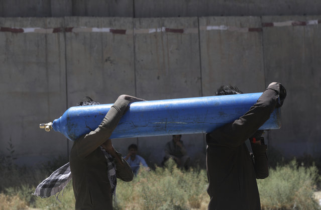 Men carry a cylinder to be refilled from a privately-owned oxygen factory, in Kabul, Afghanistan, Saturday, June 19, 2021. Health officials say Afghanistan is fast running out of oxygen as a deadly third surge of COVID worsens. (Photo by Rahmat Gul/AP Photo)