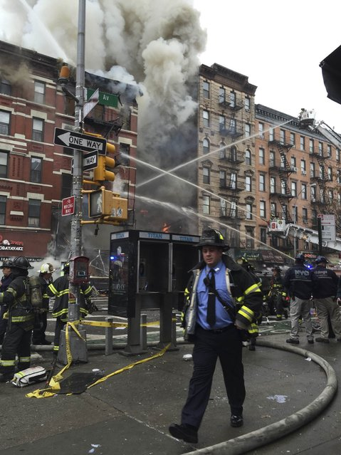 Fire officials are seen outside a building which collapsed and burst into flames at Second Avenue and East 7th Street in New York's East Village in this picture courtesy of Andrea Scarantino taken March 26, 2015. One person was injured critically and other injuries were possible, said the Fire Department of New York (FDNY). (Photo by Andrea Scarantino/Reuters)
