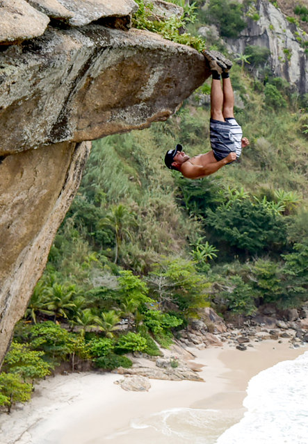 Luiz Fernando Candeia, a 27-year-old riot cop from Rio De-Janeiro shows impressive core strength by hanging from a cliff face upside down at Pedra da tartaruga, Brazil. (Photo by Caters News)