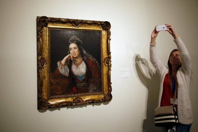 """A woman takes pictures next to """"Portrait of the writer Varvara Lizogub"""" by Russian-born artist Vasily Tropinin during an international press tour of the Malaga branch of the State Museum of Russian Art of St Petersburg, a day before its inauguration in Malaga, southern Spain March 24, 2015. (Photo by Jon Nazca/Reuters)"""