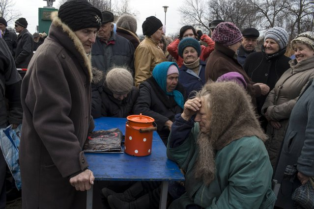 People queue for free food distributed by pro-Russian rebels in the village of Chornukhyne near the town of Debaltseve, north-east from Donetsk, March 12, 2015. (Photo by Marko Djurica/Reuters)