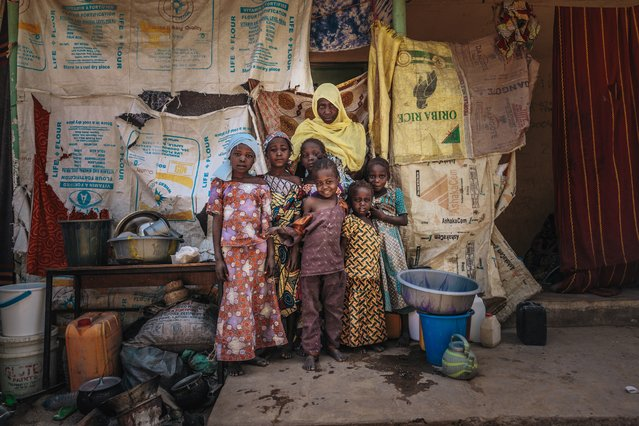 Atai and her children pose in front of their makeshift shelter in the one of the IDP camps in Maiduguri, Nigeria. It is largely constructed from burlap sacks. Atai had lived with her family, working as a tailor, in her village, Bama. Just over two years ago, Atai and her children fled when Boko Haram attached the village. Boko Haram kidnapped her daughter and killed her husband during the brutal attack. (Photo by Muse Mohammed/IOM)