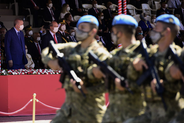 Turkish President Recep Tayyip Erdogan, back left, and Turkish Cypriot leader Ersin Tatar, second left, attend the military parade marking the 47th anniversary of the 1974 Turkish invasion in the Turkish occupied area of the divided capital Nicosia, Cyprus, Tuesday, July 20, 2021. The only route to lasting peace on ethnically divided Cyprus is through the international community's acceptance of two separate states on the east Mediterranean island nation, Turkey's president said. (Photo by Nedim Enginsoy/AP Photo)