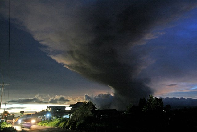In this Sunday, November 24, 2013 photo, Mount Sinabung spews volcanic ash into the air as seen from Ujung, North Sumatra, Indonesia. Authorities raised the alert status for one of the country's most active volcanoes to the highest level Sunday after the mountain repeatedly sent hot clouds of gas down its slope following a series of eruptions in recent days. (Photo by Binsar Bakkara/AP Photo)