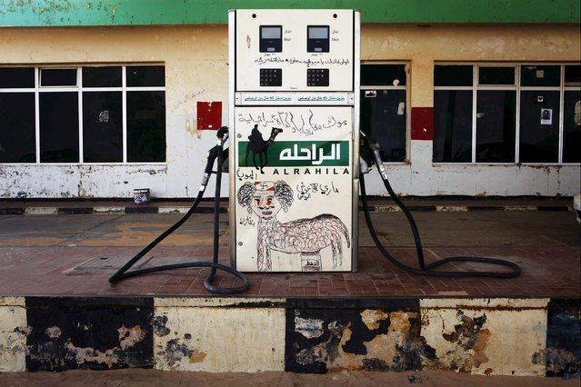 A fuel pump is defaced with a graffiti caricature of Muammar Gaddafi in the rebel-held town of Ajdabiyah March 31, 2011. (Photo by Finbarr O'Reilly/Reuters)