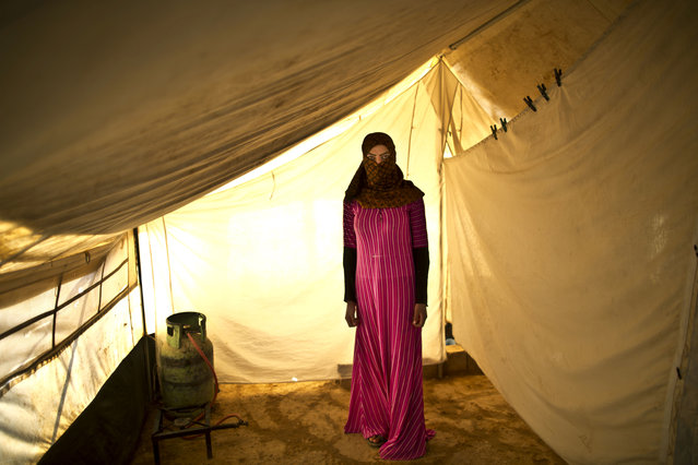 In this Monday, March 16, 2015 photo, Syrian refugee Samira Helal, 17, who is two months pregnant, poses for a portrait at  inside her tent at an informal tented settlement near the Syrian border, on the outskirts of Mafraq, Jordan. Nearly 3.8 million Syrians have fled their country and are now registered as refugees, according to the U.N. Most face increasingly desperate circumstances. (Photo by Muhammed Muheisen/AP Photo)