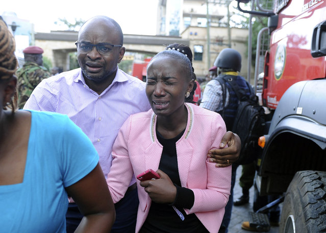 A woman cries as she is rescued from the scene at a hotel complex in Nairobi, Kenya Tuesday, January 15, 2019. Terrorists attacked an upscale hotel complex in Kenya's capital Tuesday, sending people fleeing in panic as explosions and heavy gunfire reverberated through the neighborhood. (Photo by John Muchucha/AP Photo)