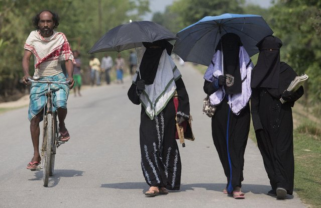 An Indian villager pedals past Burqa clad Muslim students walking to a school at Burhaburhi village about 60 kilometers (38 miles) east of Gauhati, India, Thursday, April 9, 2015. (Photo by Anupam Nath/AP Photo)