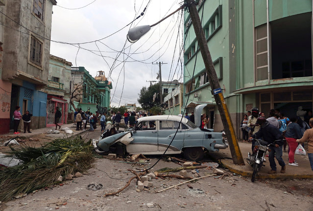 People walk past debris after a tornado ripped through a neighbourhood in Havana, Cuba on January 28, 2019. (Photo by Fernando Medina/Reuters)