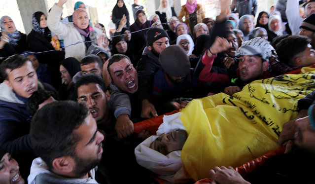 Mourners carry the body of Odeh Hamad, a 22-year-old Palestinian man, during his funeral in Beit Hanoun, northern Gaza Strip, Saturday, December 21, 2013. Health Ministry spokesman Ashraf al-Kidra in Gaza said Hamad was killed by Israeli forces when he was shot in the head on Friday near the border between Gaza and Israel. (Photo by Hatem Moussa/AP Photo)