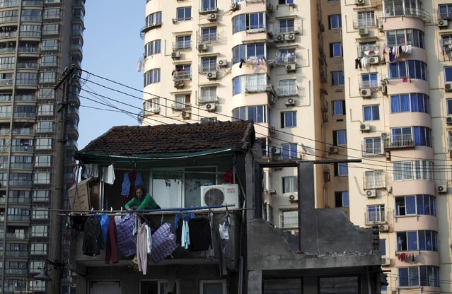 A woman stands at the balcony of her house which will be demolished to build new apartments in downtown Shanghai in this December 1, 2010 file photo. China is expected to release housing price data this week. (Photo by Carlos Barria/Reuters)