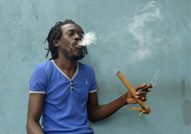 A Jamaican Rastafarian known as Nature smokes marijuana outside the Trench Town Culture Yard Museum in downtown Kingston, Jamaica, Wednesday, April 15, 2015, where he works as a tour guide. Nature, like most adherents of the Rastafarian movement, said he smokes for spiritual purposes. Drug law amendments decriminalizing small amounts of pot and paving the way for a lawful medical marijuana sector came into effect Wednesday in Jamaica. (Photo by David McFadden/AP Photo)