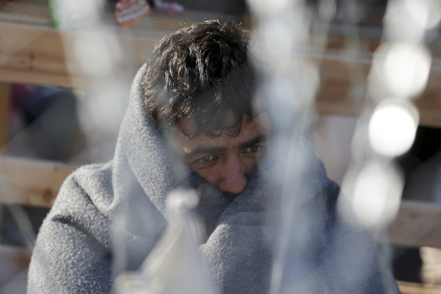A migrant waits behind a border fence at the Greek-Macedonian border, after additional passage restrictions imposed by Macedonian authorities left hundreds of them stranded near the village of Idomeni, Greece, February 23, 2016. The picture was taken from the Macedonian side of the border. (Photo by Marko Djurica/Reuters)