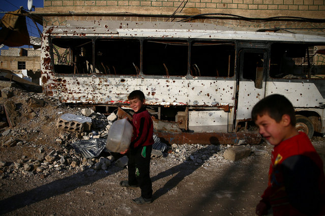 Boys walk past a damaged bus in the rebel held besieged Douma neighbourhood of Damascus, Syria January 17, 2017. (Photo by Bassam Khabieh/Reuters)