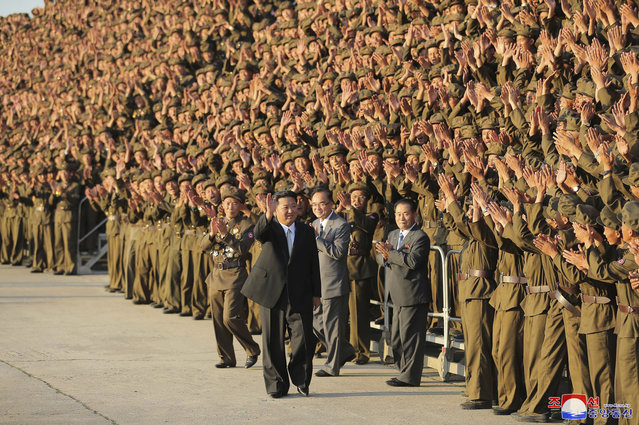 In this photo provided by the North Korean government, North Korean leader Kim Jong Un, center, waves to participants as they gather for a group photo, in a celebration of the nation's 73rd anniversary at Kim Il Sung Square in Pyongyang, North Korea, Thursday, September 9, 2021. (Photo by Korean Central News Agency/Korea News Service via AP Photo)