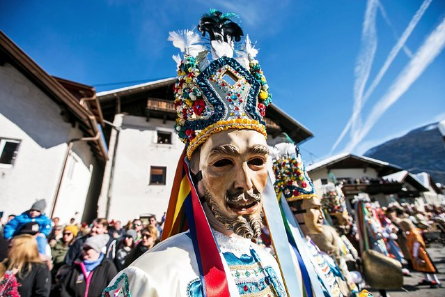 """Participants wearing brightly-colored costumes and painted, wooden masks participate in the """"Nassereither Schellerlaufen"""" parade to chase away winter on February 17, 2019 in Nassereith near Telfs, Austria. The event dates back 270 years, only occurs every three years and is part of Shrove Tuesday tradition common across the Alemannic region of western Tyrol, Switzerland, Alsace and southwestern Germany. Shrove Tuesday, called Fasnacht in German, is celebrated with similar parades throughout the region in the weeks before the actual Shrove Tuesday date, which this year is March 5. (Photo by Jan Hetfleisch/Getty Images)"""