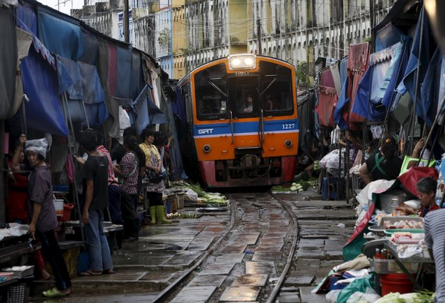 Thai vegetable market vendors pull back awnings and their produce off a railway track to allow a cross-country train to dissect through the middle of the town of Maeklong, in Samut Songkhram province, 60 km (37 miles) west of Bangkok in this August 16, 2012 file photo. (Photo by Chaiwat Subprasom/Reuters)