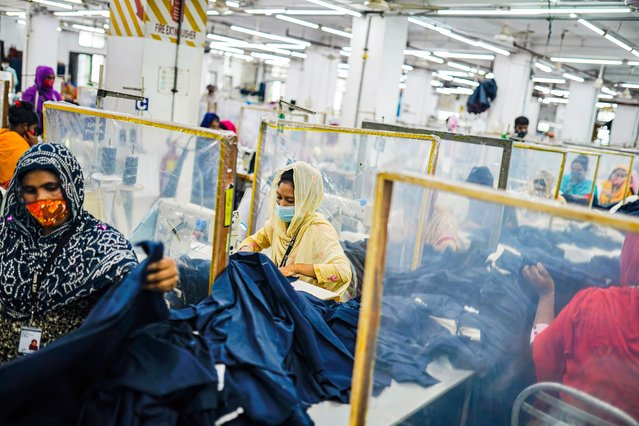 Ready Made Garment (RMG) workers separated by polythene barriers to maintain social distance during their worker as a precaution against the spread of corona virus in Dhaka, Bangladesh on August 9, 2021. (Photo by Sultan Mahmud Mukut/SOPA Image/Rex Features/Shutterstock)