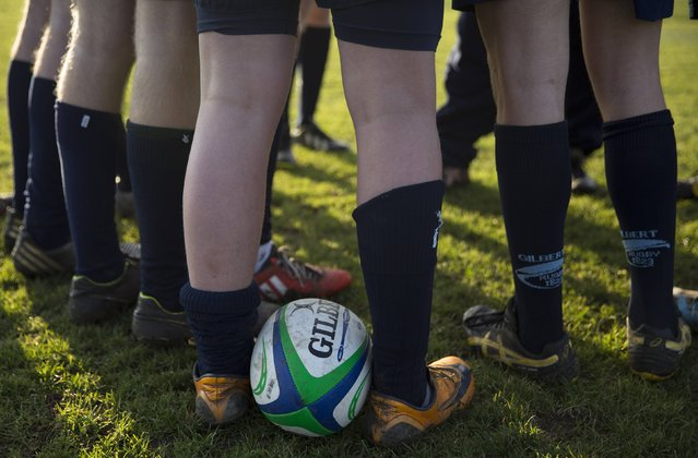 A ball lies between a pupil's feet as he takes part in rugby practice on the playing fields of Rugby School in central England, January 20, 2015. (Photo by Neil Hall/Reuters)