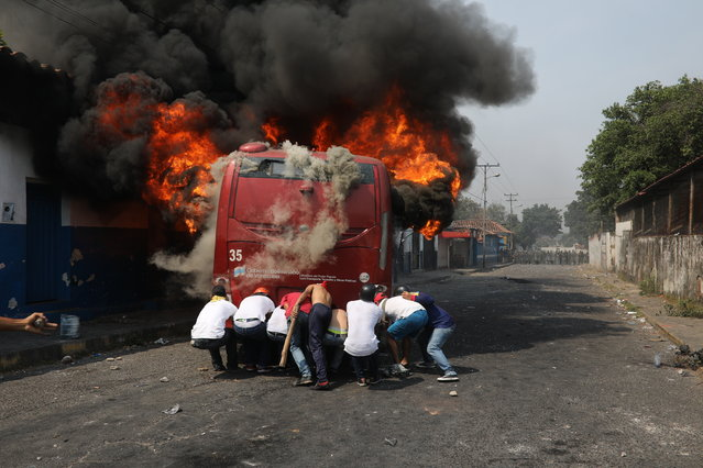Demonstrators push a bus that was torched during clashes with the Bolivarian National Guard in Urena, Venezuela, near the border with Colombia, Saturday, February 23, 2019. Venezuela's National Guard fired tear gas on residents clearing a barricaded border bridge between Venezuela and Colombia on Saturday, heightening tensions over blocked humanitarian aid that opposition leader Juan Guaido has vowed to bring into the country over objections from President Nicolas Maduro. (Photo by Rodrigo Abd/AP Photo)