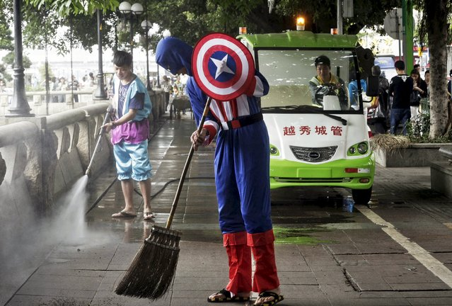 A student volunteer in a Captain America costume (front) sweeps the ground during a campaign to clean the streets to mark Earth Day, in Guangzhou, Guangdong province April 21, 2015. Earth Day, which promotes awareness about the necessity of conserving the environment, is celebrated annually on April 22. (Photo by Reuters/Stringer)