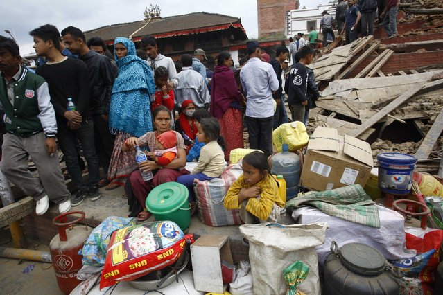 In this photo provided by China's Xinhua News Agency, people gather beside damaged buildings after an earthquake in Kathmandu, capital of Nepal, Saturday, April 25, 2015.  A strong earthquake shook Nepal's capital and the densely populated Kathmandu Valley before noon Saturday, causing extensive damage with toppled walls and collapsed buildings, officials said. (Photo by Pratap Thapa/Xinhua via AP Photo)