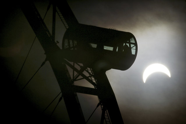 A partial solar eclipse is seen behind a passenger capsule of the Singapore Flyer Wednesday, March 9, 2016, in Singapore. The last eclipse happened in Singapore in January, 2009 and the next solar eclipse, an annular one, will occur on December 26, 2019. (Photo by Wong Maye-E/AP Photo)