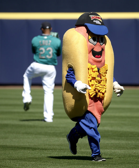 A mascot taking part in a race runs past Seattle Mariners' Nelson Cruz during the third inning of a spring training baseball game against the Kansas City Royals Wednesday, March 9, 2016, in Peoria, Ariz. (Photo by Charlie Riedel/AP Photo)
