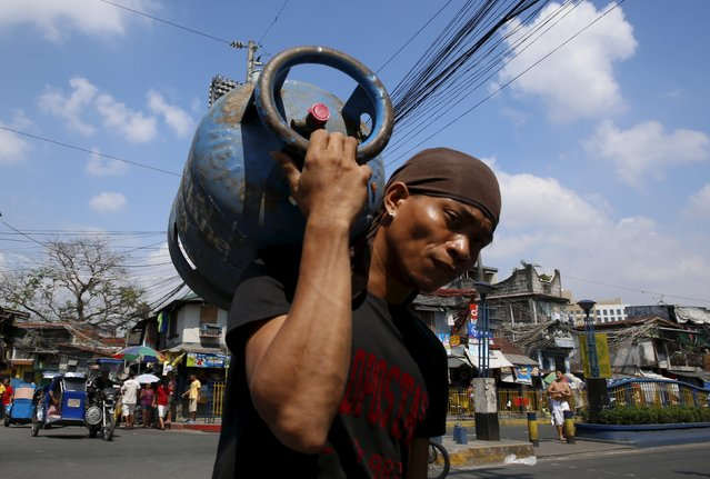 A man carries a tank containing LPG cooking fuel along a street, in Mandaluyong, Metro Manila March 5, 2016. (Photo by Erik De Castro/Reuters)