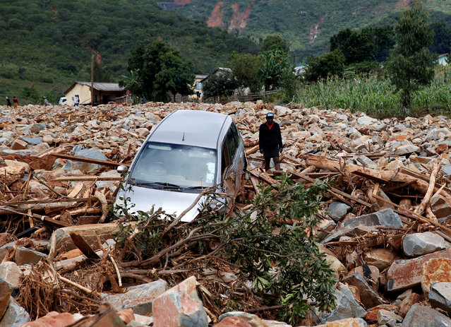 A woman stands besides a car that was swept away with debris by Cyclone Idai in Chimanimani, Zimbabwe, March 23,2019. Cyclone Idai smashed into the coast of central Mozambique last week, unleashing hurricane-force winds and rains that flooded the hinterland and drenched eastern Zimbabwe leaving a trail of destruction. (Photo by Philimon Bulawayo/Reuters)