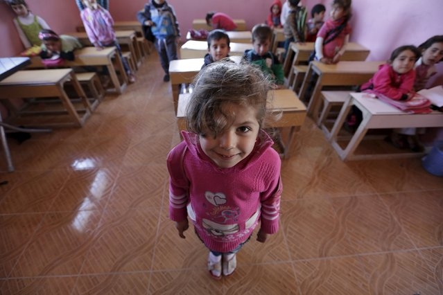 Five-year-old Jana Mahmoud poses inside a classroom in the rebel-controlled area of Maarshureen village in Idlib province, Syria, March 12, 2016. (Photo by Khalil Ashawi/Reuters)