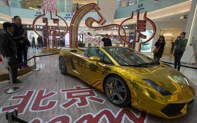A gold Lamborghini luxury sports car is displayed at a mall with a price tag of 4.9 million yuan (US $808,000) in Beijing, China, Monday, February 17, 2014. (Photo by Ng Han Guan/AP Photo)