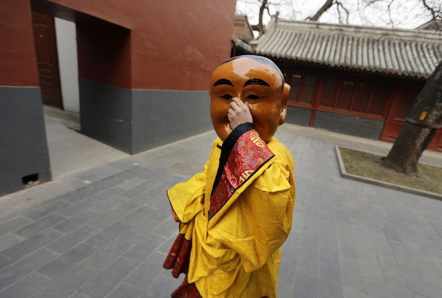 """A Tibetan monk adjusts his mask as he arrives for a religious ceremony, known as """"Da Gui"""" or beating ghost, to celebrate the upcoming Tibetan New Year which starts on March 1 at Yonghegong Lama Temple, in Beijing, on February 28, 2014. (Photo by Jason Lee/Reuters)"""