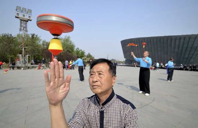 """A man spins a Chinese traditional top, called """"kongzhu"""", at a square in Handan, Hebei province, China, April 26, 2015. More than 50 fans perform at a local Kongzhu event on Sunday, according to local media. (Photo by Reuters/Stringer)"""