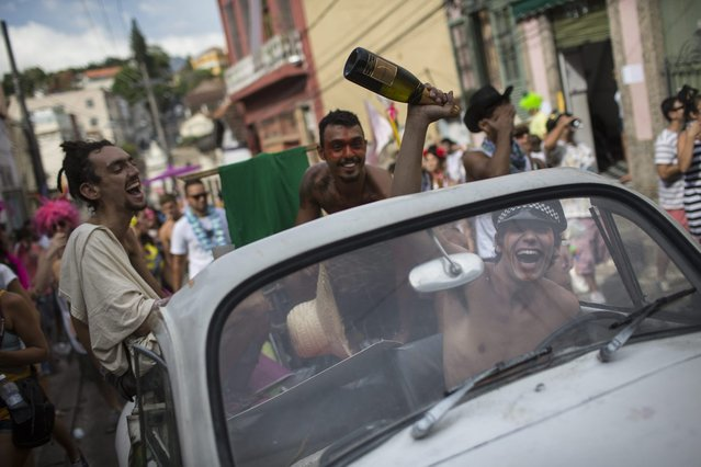 "A reveler holds a bottle of sparkling wine as he drives a car at the ""Ceu na Terra"" block party during Carnival celebration in Rio de Janeiro, Brazil, Saturday, March 1, 2014. Rio de Janeiro's over-the-top Carnival is the highlight of the year for many local residents. Hundreds of thousands of merrymakers will take to Rio's streets in the nearly 500 open-air ""bloco"" parties. (Photo by Felipe Dana/AP Photo)"