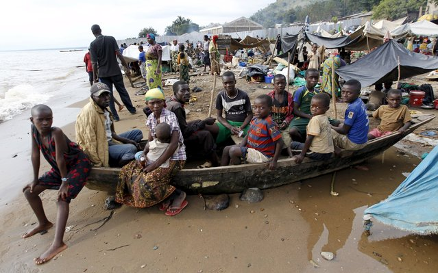 Burundian refugees sit on a wooden boat on the shores of Lake Tanganyika in Kagunga village in Kigoma region in western Tanzania, as they wait for MV Liemba to transport them to Kigoma township, May 18, 2015. (Photo by Thomas Mukoya/Reuters)